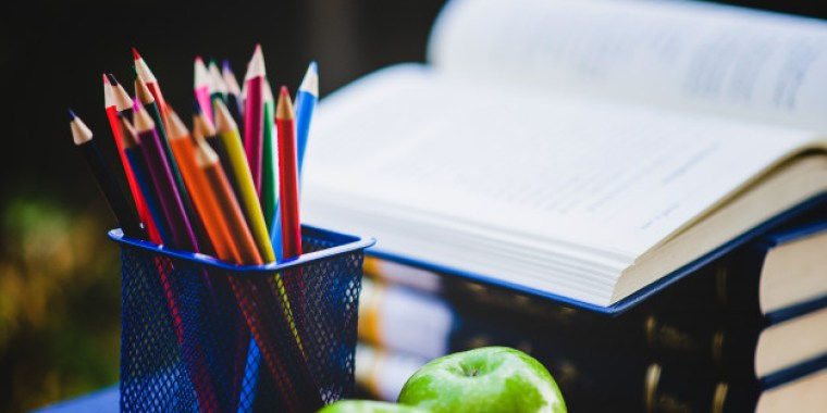 Books, pencils and 2 green apples on a study desk.