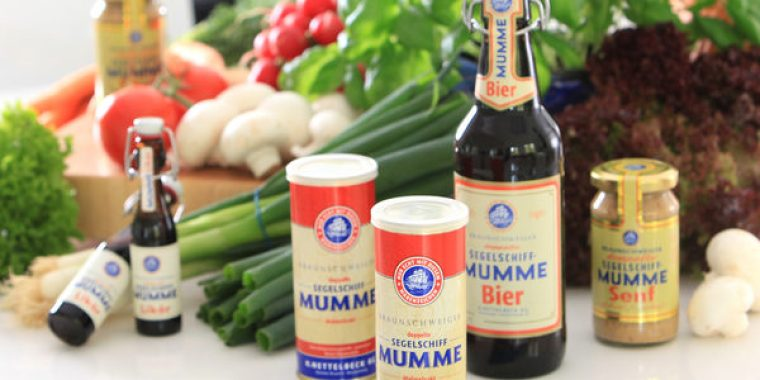 Products from Braunshweiger Mumme brands with some tomatoes, mushrooms and spring onions in the background.