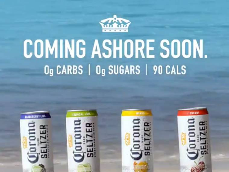 An advertising ad for a Corona Seltzer with four cans of Seltzer on a beach shore.