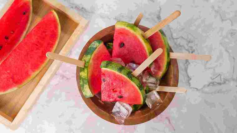 Slices of fresh watermelon and watermelon on wooden sticks mixed with ice cubes.