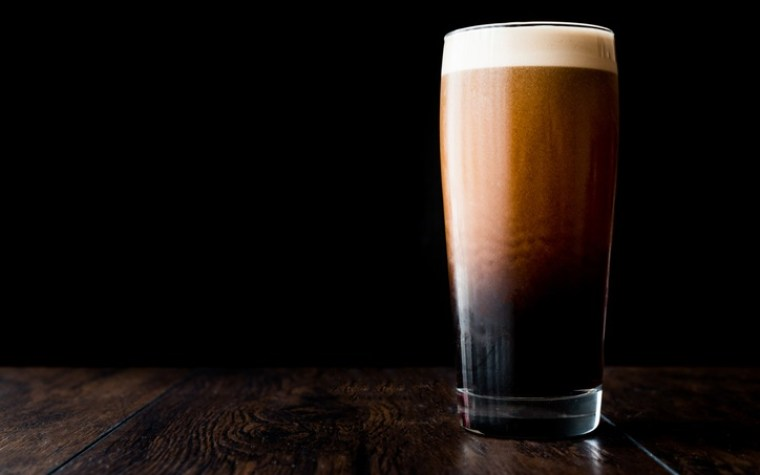 A glass of stout beer in the black background.