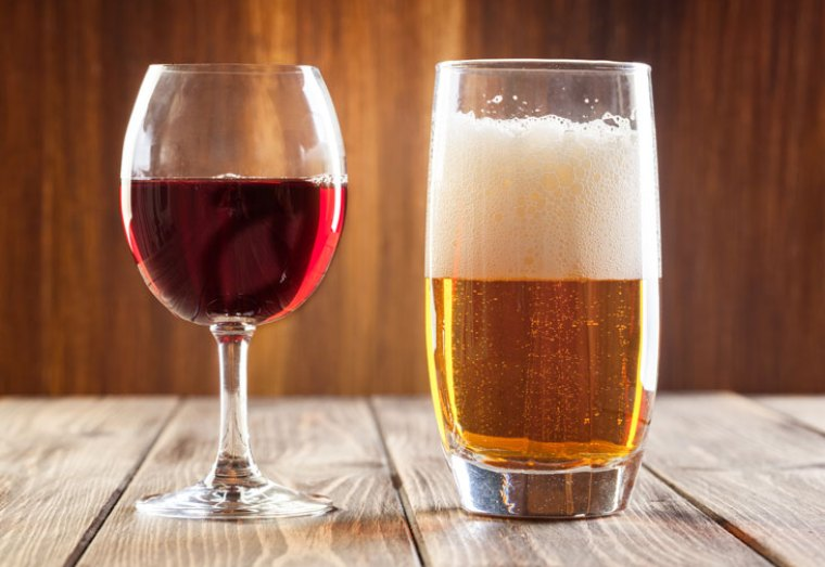 A glass of red wine and a glass of beer on a table.