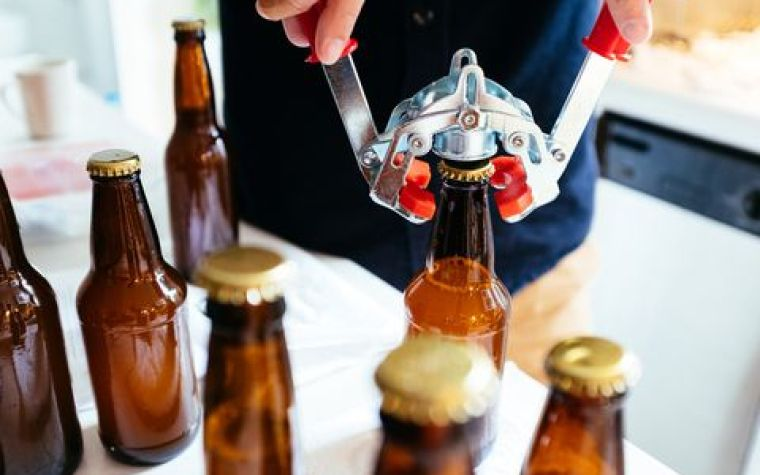 Capping a bottle of beer with a winged capper and other brown bottles standing near by.