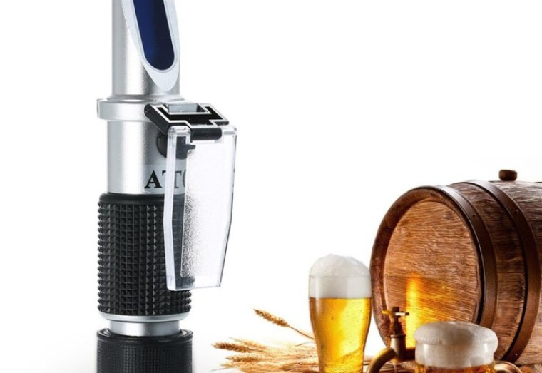 A refractometer, wooden cask for beer brewing, wheat, small bowl of hops, glass of beer and a mug of beer