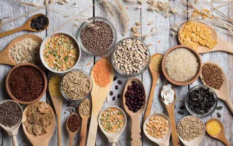 Different types of whole grains and seeds places of wooden spoons.