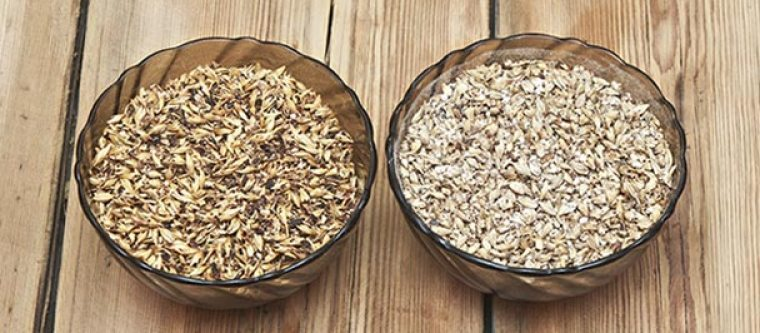 A bowl of whole grains next to a bowl of slightly crushed grains.