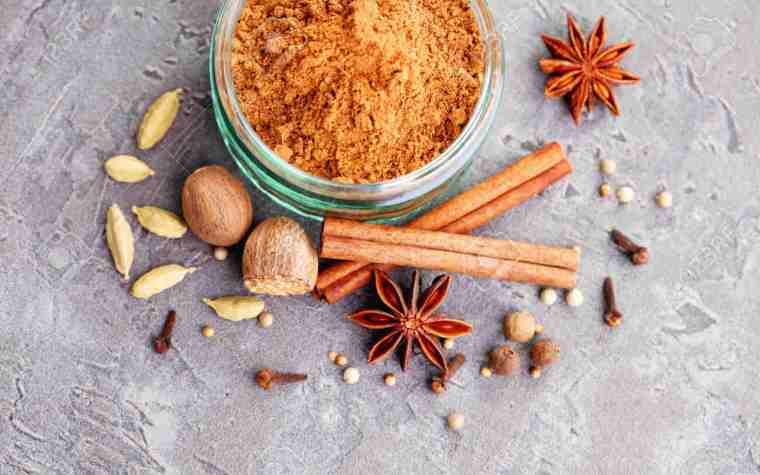 A bowl of grounded ginger with star anise, cinnamon sticks, nutmeg, almonds and other spices.