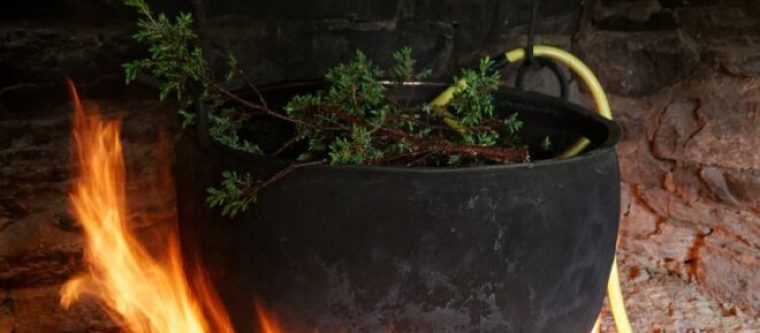 A clay pot filled with herbs and plants put on the open fire.