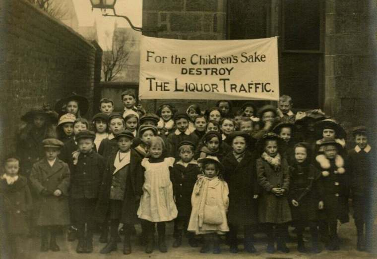 A gathering of small children under a banner asking for prohibiton of alcohol.