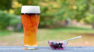 A glass of beer and a small bowl of fresh blueberries with a spoon