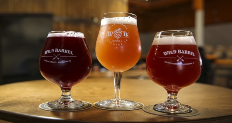 Three glasses of sour beer each with different color and flavoring.