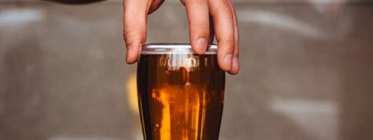 A hand holding a glass of beer by the top.