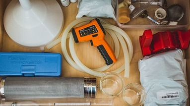 Various brewing tools including tubing and an infrared thermometer.