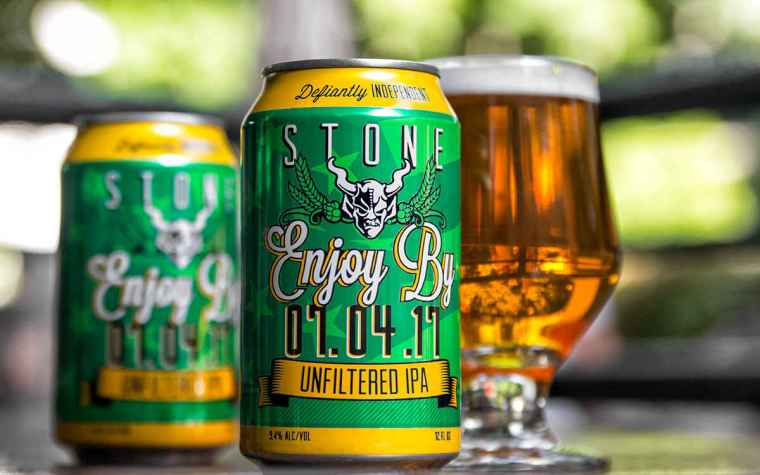 Two cans and a glass of Enjoy By IPA beer.