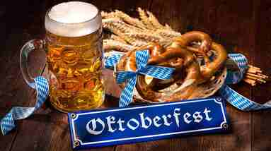 A mug of beer, some pretzels, dry wheat and an Oktoberfest sign.