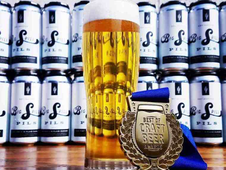 A glass of lager beer with a medal and a row of beer cans in the background.