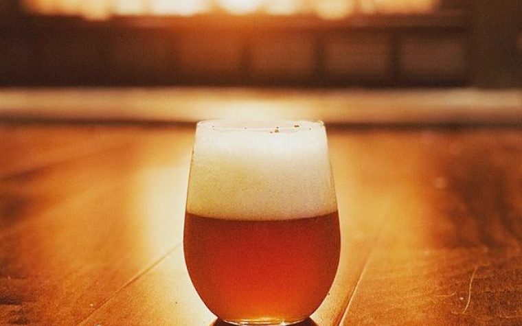 A glass of West Coast IPA beer on a table.