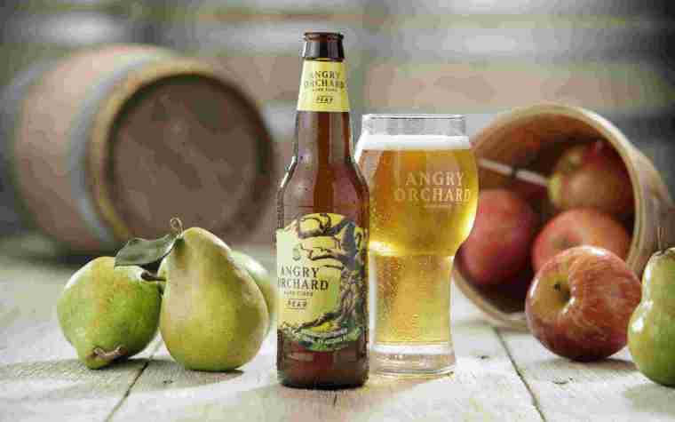 A bottle and a glass of pear cider with fresh pears and a bowl of apples on the table.