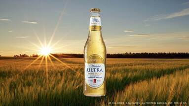A bottle of Michelob Ultra Pure Gold beer in a wheat field.