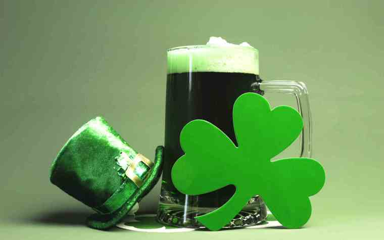 A mug of dark beer with a four leaf clover and a leprechaun hat.