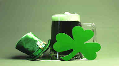A mug of dry Irish stout beer with a green four leaf clover and a leprechaun hat.