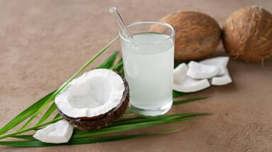 A glass of coconut water and opened coconuts.