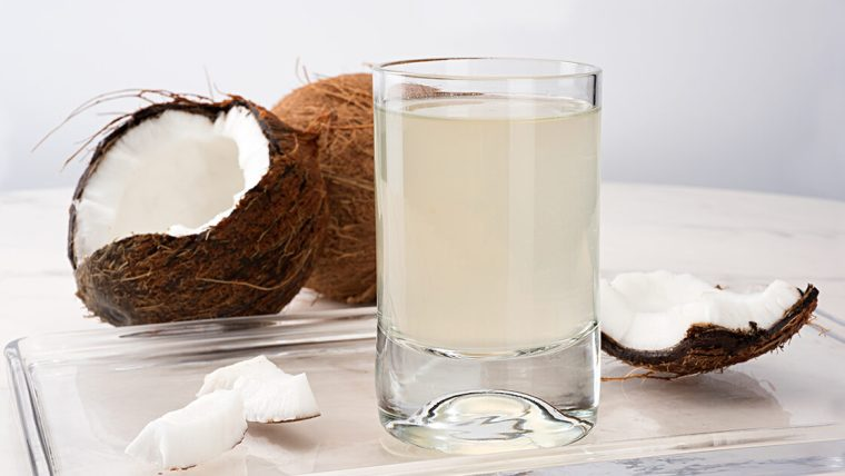A glass of coconut water on a glass tray with an opened coconut.