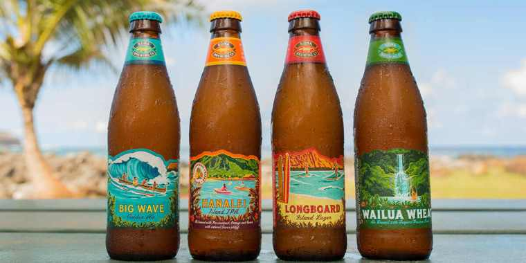 Four bottles of beer placed in a tropical setting.