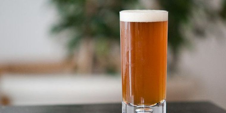 A glass of amber color American Pale Ale beer style.