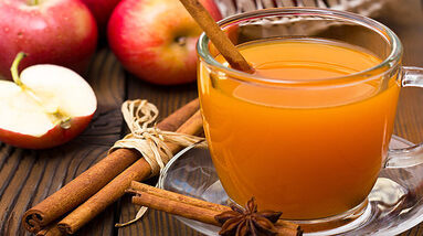 A cup of apple cider, cinnamon sticks, cloves and fresh red apples on the table.