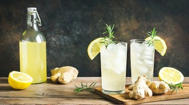 A bottle and glasses of fermented lemonade with sliced lemons and ginger roots.