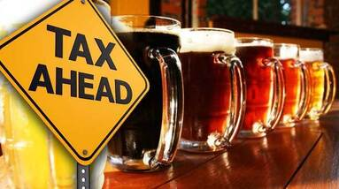 A row of beer mugs and a yellow sign warning of a tax ahead.
