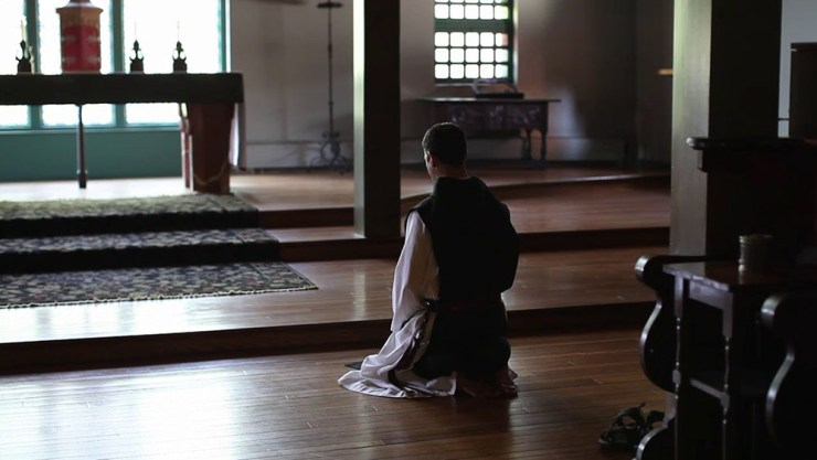 A trappist monk sits in silence.