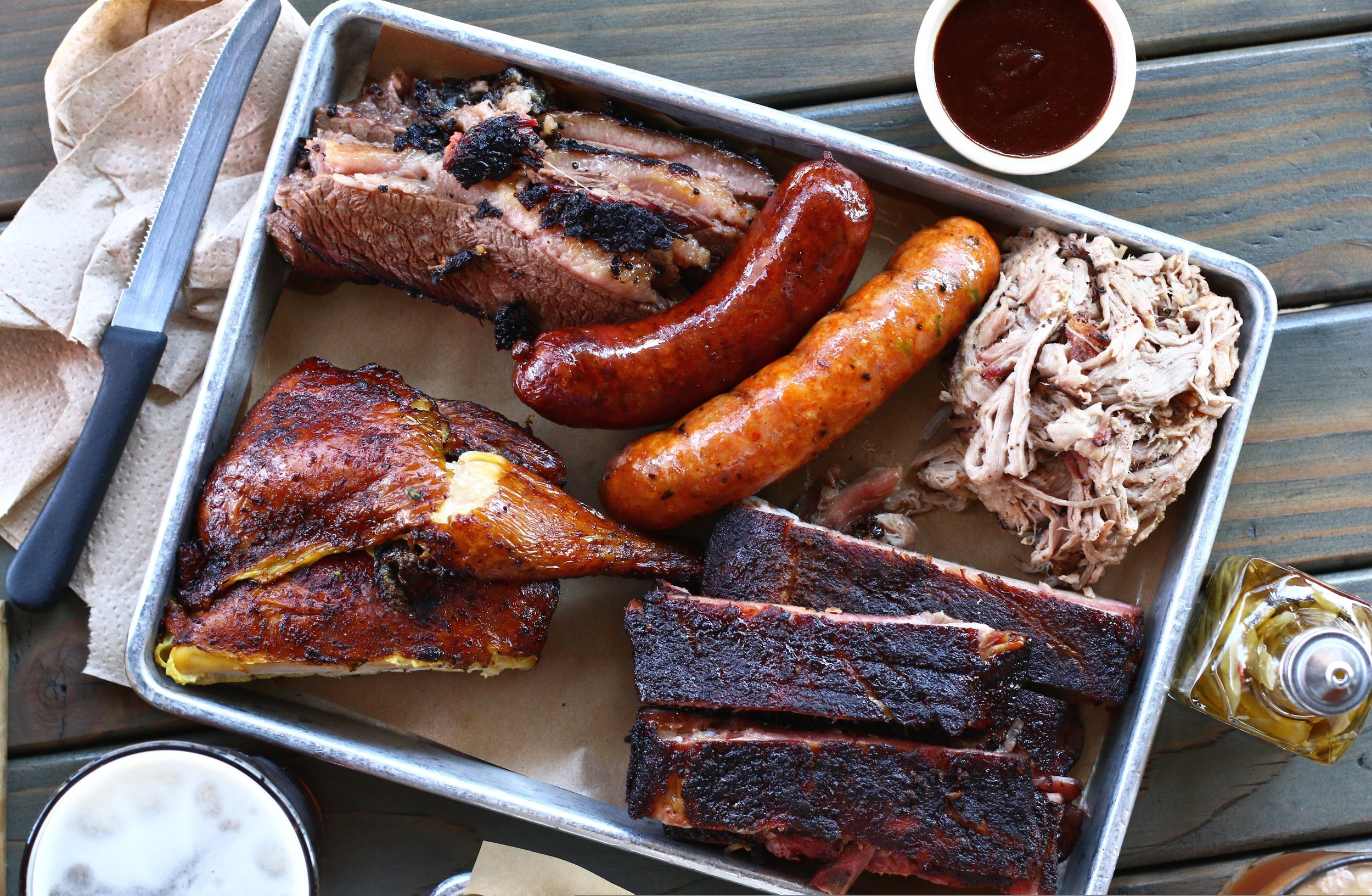 A sheet pan of smoked meats from Bludso's Bar and Que