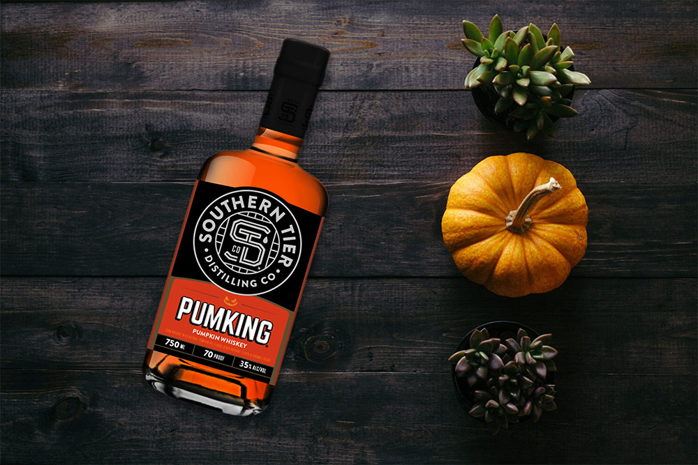 A bottle of Southern Tier Pumking Whiskey next to a pumpkin.