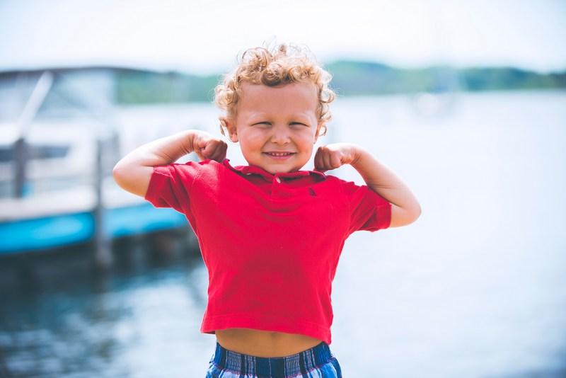 Little boy flexing his muscles