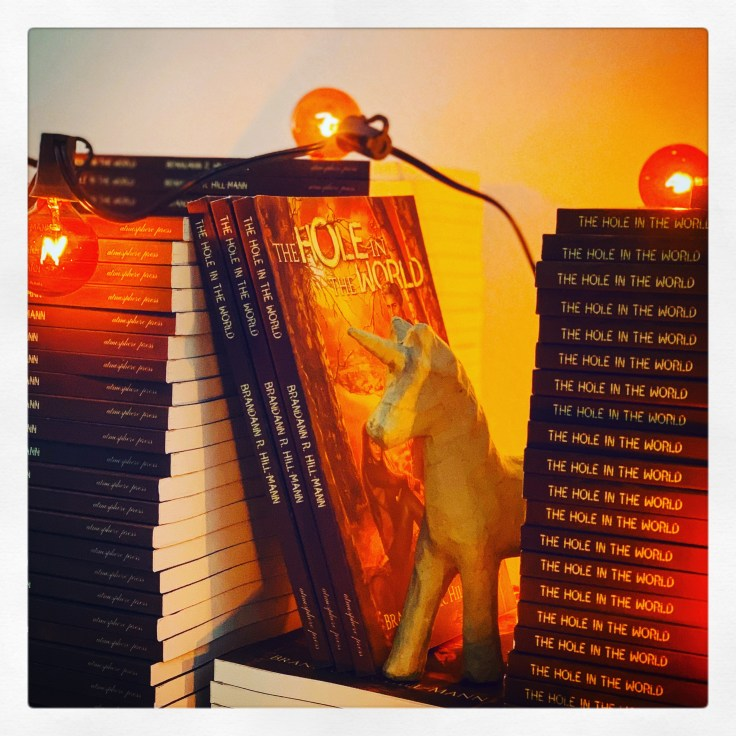 Several stacks of the book The Hole in the World, adorned with orange lights and a little kraft paper unicorn.