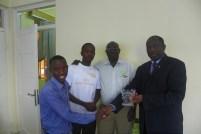 Brian Matovu and Mugaga Julius presenting the award to the Principal of the College of health sciences at Makerere University.