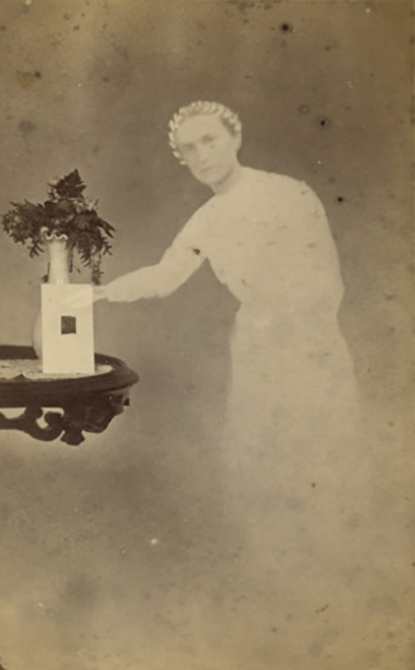 """[Female """"spirit"""" standing next to a table with a photograph propped against a vase with flowers]; William H. Mumler (American, 1832 - 1884); 1862–1875; Albumen silver print; 9.8 × 5.7 cm (3 7/8 × 2 1/4 in.); 84.XD.760.1.33; No Copyright - United States (http://rightsstatements.org/vocab/NoC-US/1.0/)"""