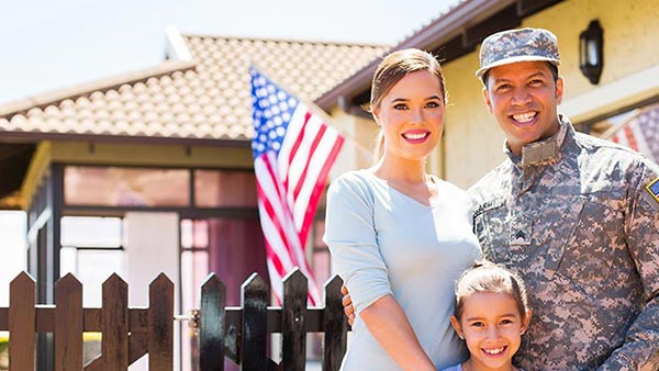 Veteran with family in front of home from a VA home loan