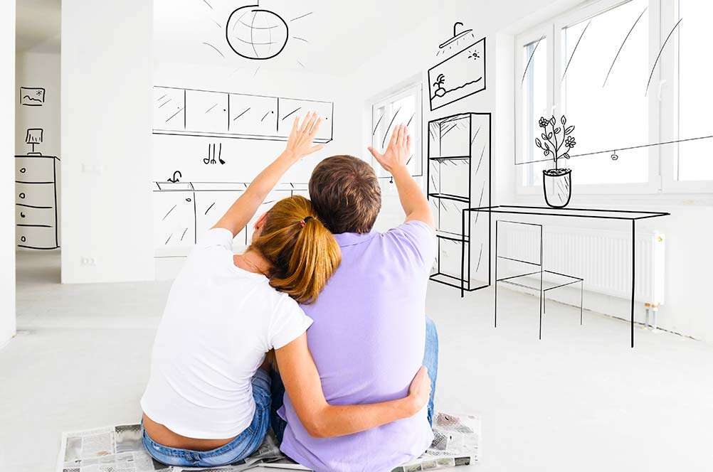Young couple sitting on the floor visualizing a home remodel with an FHA 203K mortgage refinancing option.