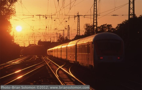 Deutche Bahn InterCity train 522 Berchtesgadener Land (Berchtesgaden—Hamburg) catches the glint of the setting sun at Bonn, Germany. Compare this view with that of Amtrak's Lake Shore Limited catches the glint at Palmer, May 28, 1986. (posted December 7, 2012). Exposed on Fuji Sensia II (ISO 100) slide film using a Nikon F3T fitted with f2.8 135mm lens. Exposure calculated manually with a handheld Sekonic Studio deluxe light meter (approximately f8 1/500 sec).