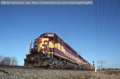 Wisconsin Central SD45 loom large as the lead a southward freight out of the siding at Byron, Wisconsin on March 23, 1996.