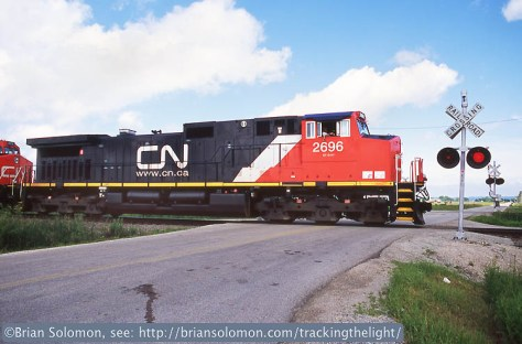 A Canadian National DASH9-44CW hits the Subway Road crossing in North Fond du Lac, Wisconsin on a June 2004 afternoon. Exposed with a Nikon F3T fitted with a 24mm lens.