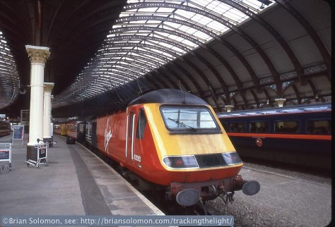 The unusual curved York train shed was built between 1871 and 1877. A Virgin Cross Country HST pauses at York on 4 July 1999. This was led by one of the less-common varieties of the Class 43 power units that featured buffers. Exposed on Fujichrome Sensia using a Nikon N90S with 24mm lens.