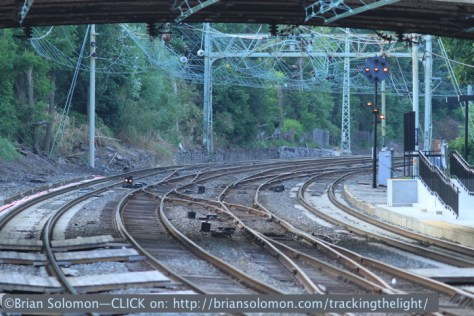The interlocking at Overbrook is a vestige of steam-era railroad engineering. Today railroads wouldn't consider placing crossovers on curve in the middle of a busy station with low level platforms. Note the signal displaying 'Restricting' with a classic PRR aspect. Canon EOS 7D with 200mm lens. July 1, 2014.