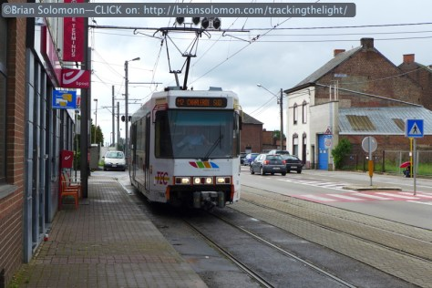 Streetside pickup point; an inbound tram pauses for a stop to collect passengers in Anderlues. Lumix LX7.