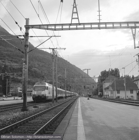 Sun streams through the clouds as an eastward SBB train glides through the station at Visp, Switzerland in June 2001. Exposed on 120 size black & white film using a Rolleiflex Model T.