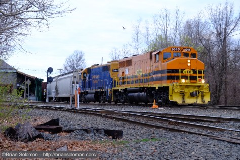On evening of May 1, 2015, a northward New England Central freight crosses the Palmer diamond with locomotive 3015 in the lead. Exposed with a Fujifilm X-T1.