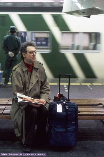 Richard J. Solomon with newspaper waiting on a railway platform in Tokyo on April 23, 1997.
